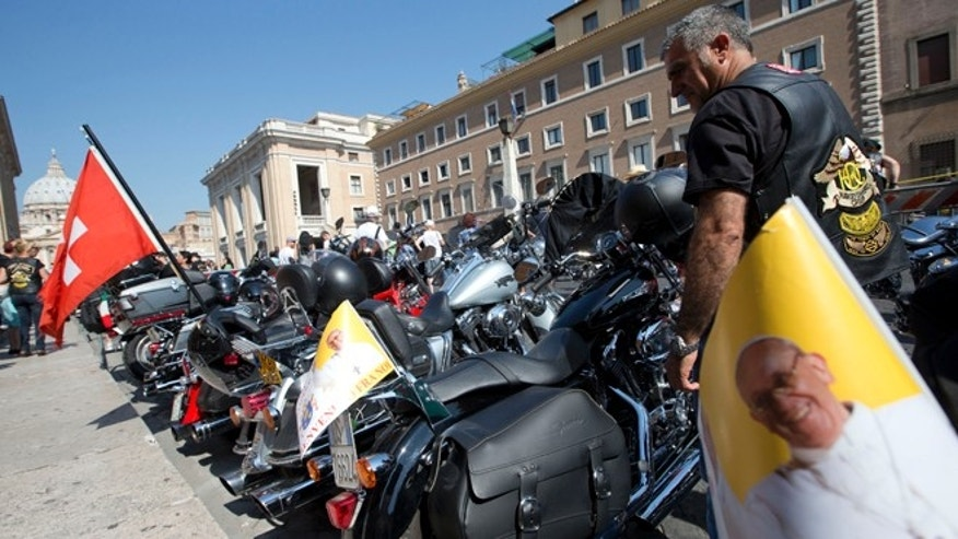 Harley Davidson motorcycles riders park their motorcycles in Via della Conciliazione leading to the Vatican, seen at left, as they wait for Pope Francis to drive by to bless them ahead of mass in St. Peter's Square, at the Vatican, Sunday, June 16, 2013. The riders are gathered in Rome for a four-day event to celebrate the motorcycle company's 110th anniversary.  (AP Photo/Andrew Medichini)