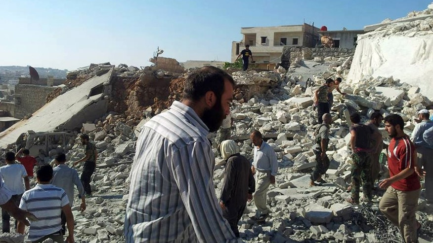 Syrian citizens standing on rubble of destroyed houses that were damaged by Syrian forces airstrike in Aleppo.
