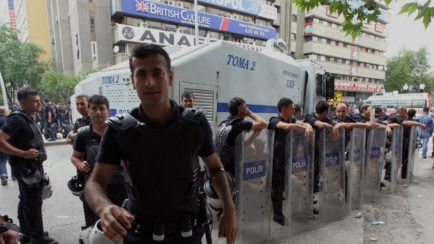 June 17, 2013 - A police officer reacts to cameras as others stand during a rally by the labor unions in Ankara, Turkey.