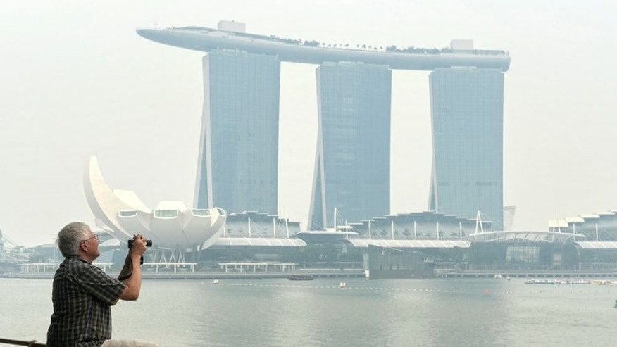 A tourist takes pictures in front of the Marina Bay Sands hotel as it is blanketed by haze, in Singapore, on June 17, 2013. Smog from forest fires in Indonesia stayed at unhealthy levels in Singapore on Tuesday as the two neighbours blamed each other for the seasonal problem.