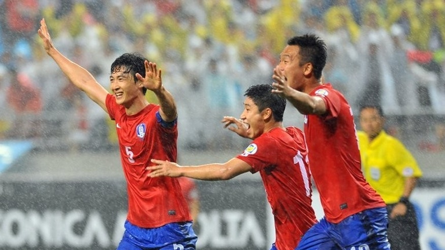 South Korean players celebrate Uzbekistans defender Shorakhmedov Akmal's own goal during their World Cup qualifier in Seoul on June 11, 2013. South Korea won the match 1-0 and face Iran on Tuesday.