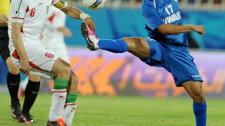 "Kuwait's Bader al-Mutawaa (R) battles for the ball with Iran's skipper Javad Nekounam on March 26, 2013. South Korea's promise to ""make life painful"" for Iran and to force their captain to cry ""tears of blood"" have sharply raised the stakes before Tuesday's clash between the Asian giants in Ulsan."