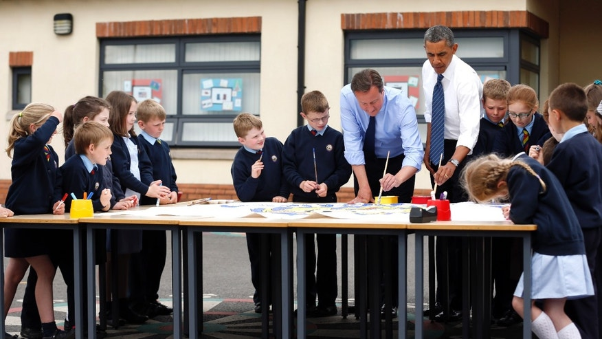 June 17, 2013 - President Barack Obama and British Prime Minister David Cameron help students as they work on a school project about the G-8 summit during a visit to the Enniskillen Integrated Primary School in Enniskillen, Northern Ireland.
