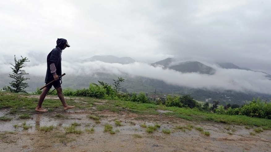 A farmer walks home at Khokana village on the outskirts of Kathmandu during the monsoon on July 19, 2012. At least 12 people have been killed in landslides triggered by three days of heavy monsoon rain in remote parts of Nepal, officials said Tuesday.