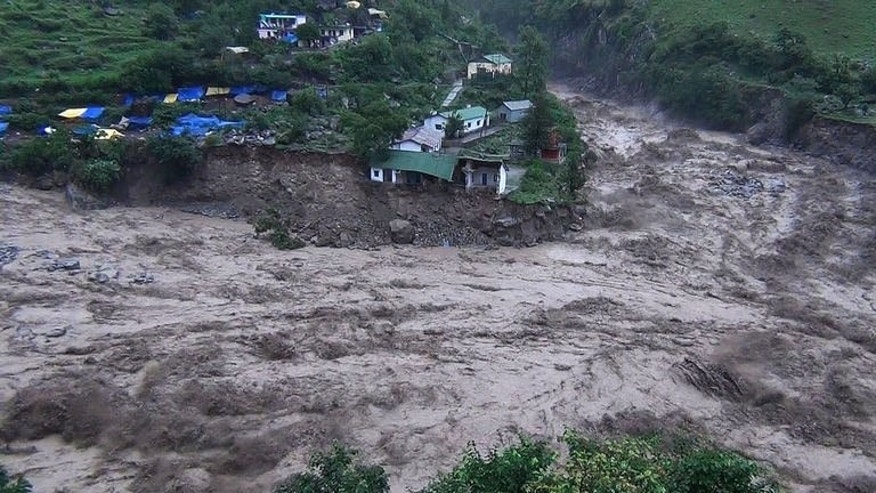 Houses perch precariously as river banks collapse from the rising waters of a flooded river in the northern state of Uttarakhand, on June 17, 2013. Torrential rains have triggered flash floods and landslides in northern India, leaving at least 60 people feared dead and thousands stranded after the monsoon covered the country ahead of schedule.
