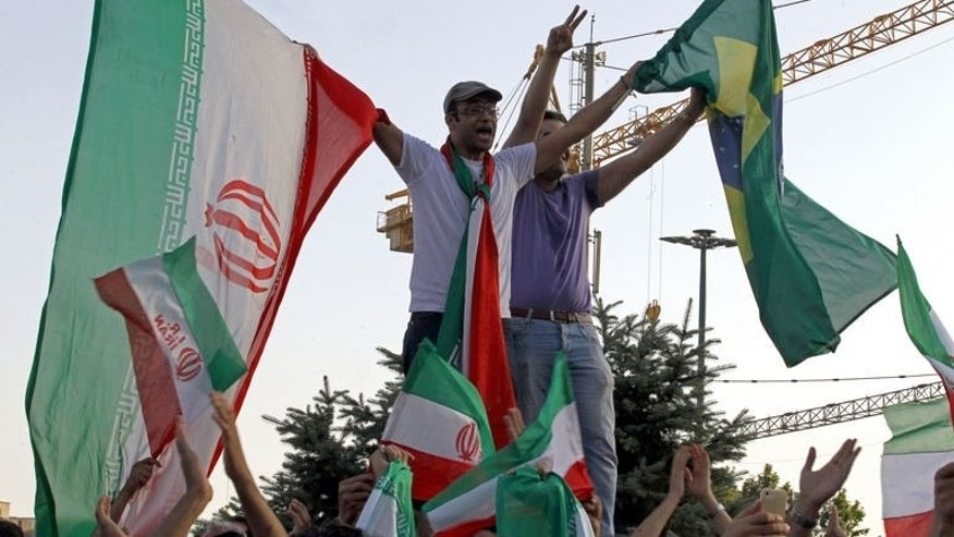 Iranian football fans hold their national flag (L) and the Brazilian flag (R) as they celebrate at Vanak square in northern Tehran on June 18, 2013 after Iran won their 2014 World Cup Asian zone group A qualifying football match against South Korea.