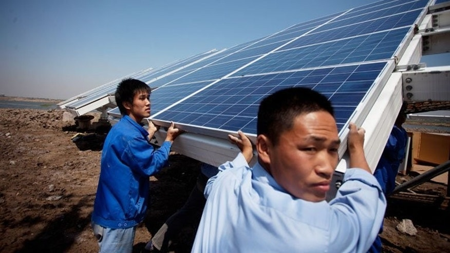 Wokers install solar panels at the Sino-Singapore Eco-city near Tianjin. China said Tuesday it will this week hold talks with the European Union in a bid to resolve a dispute over solar panels and other business issues, as tensions between the two risk escalating into a trade war.