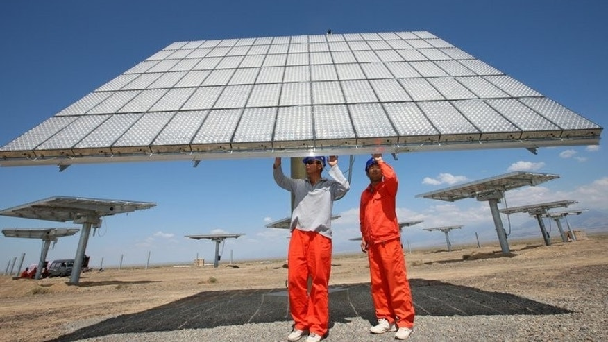 Workers check on a solar panel in a field in Hami, China's farwest Xinjiang region. The European Commission, the EU's executive arm, has levied an initial average tariff of 11.8% on Chinese solar panels, which will rise to 47.6% on August 6 if there are no negotiations based on a Chinese commitment to address the problem.
