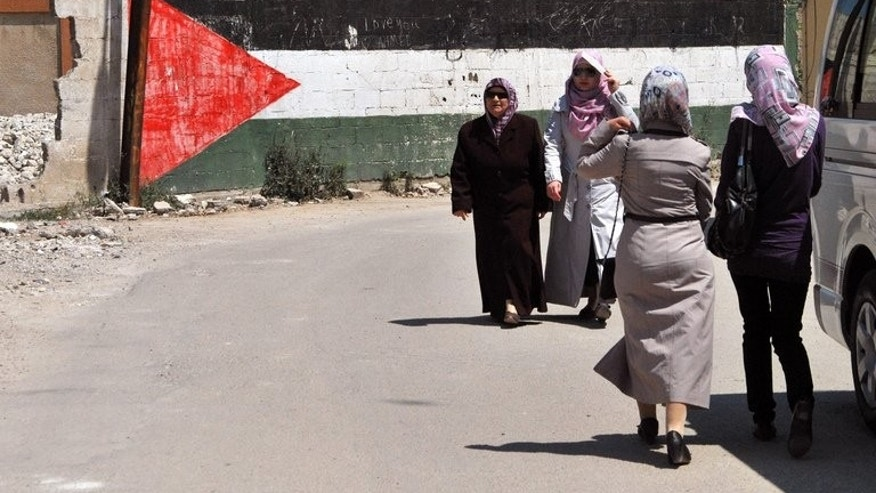 Women walk past a giant Palestinian flag painted on a wall at a camp for Palestinian refugees in Homs, Syria on May 22, 2013. The conflict in Syria has displaced more than two-thirds of Palestinian refugees living in the country, the UN Relief and Works Agency for Palestine refugees said