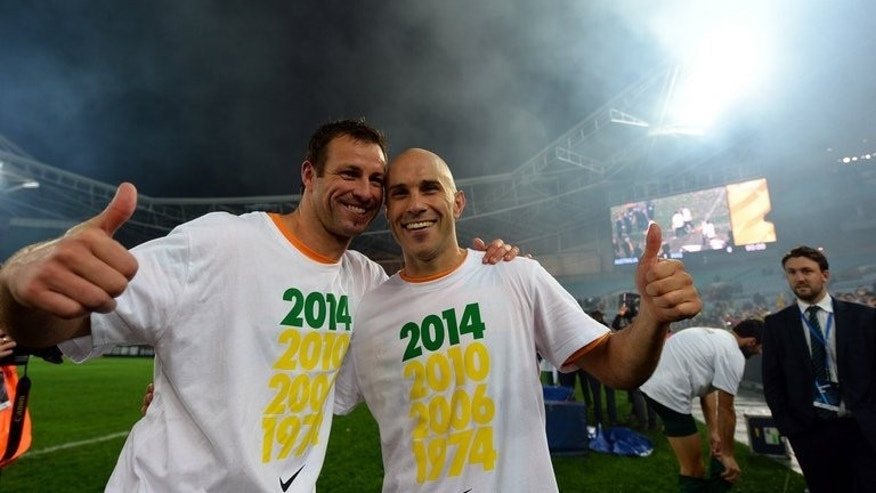 Australia's captain Lucas Neill (L) celebrates victory with teammate Mark Bresciano after defeating Iraq in the World Cup qualifier in Sydney, on June 18, 2013. Coach Holger Osieck claimed vindication for his methods after Australia qualified for the Cup with a last-gasp header.