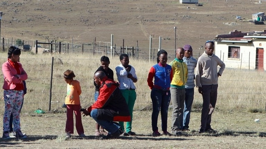 A picture taken on June 16, 2013 shows Mandla Mandela (3rd L), grandson of former South African president Nelson Mandela, kneeling down to talk to a young girl from the village of Mvezo. Mandla wanted to be a disc jockey but his illustrious grandfather had other ideas for him -- passing down a lesson on the responsibility that South Africa's most famous surname carries.