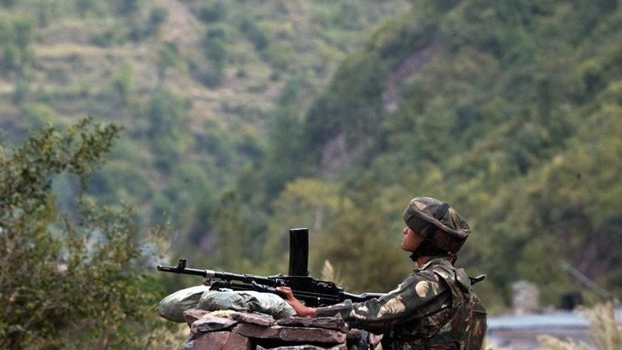 An Indian army soldier looks towards the Pakistani side on the Indian side of Line of Control (LOC) near Kaman post on October 9, 2008. A Pakistani woman was injured Tuesday when Indian troops fired across the disputed border in the Himalayan region of Kashmir, Pakistan's military said.