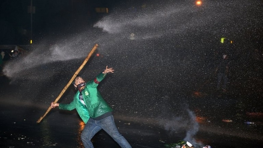 A student hurls a bamboo stick as police spray a water cannon during a protest against the fuel price hike, outside the parliament in Jakarta, on June 17, 2013. Indonesia defied popular anger on Tuesday by pressing ahead with its first fuel price hike since 2008, a day after police fought running battles with thousands outside parliament.