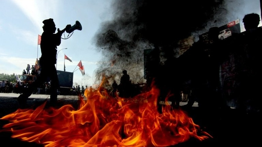 Demonstrators burn tyres during a protest against the fuel price hike, in Makassar, on Sulawesi island, on June 17, 2013. Indonesia defied popular anger on Tuesday by pressing ahead with its first fuel price hike since 2008, a day after police fought running battles with thousands outside parliament.