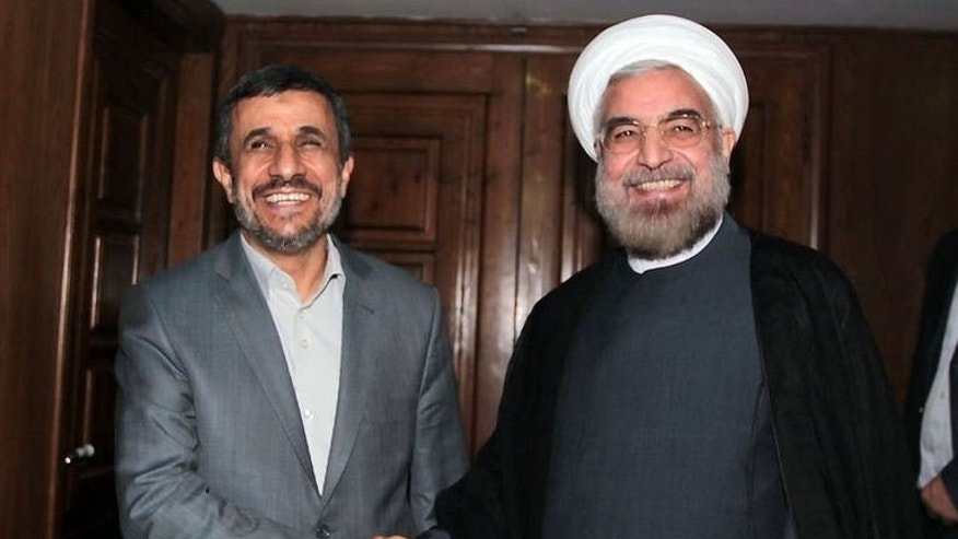 Outgoing president Mahmoud Ahmadinejad (left) shakes hands with Iranian president-elect Hassan Rowhani in Tehran on June 18, 2013. Ahmadinejad met his successor Hassan Rowhani on Tuesday for the first time since the moderate conservative was elected, in talks centred on political and economic issues.