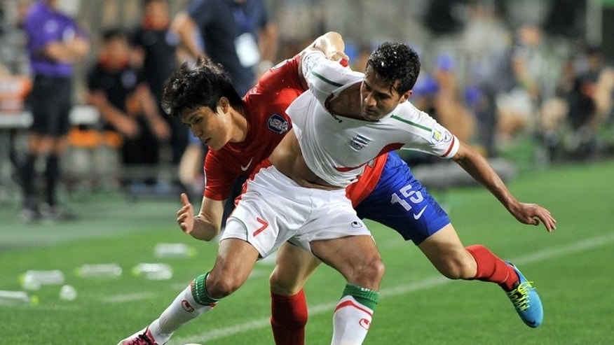 South Korea's defender Kim Chang-Soo (back) competes for the ball with Iran's midfielder Masoud Shojaei during their World Cup Asian qualifier match in Ulsan, southeast of Seoul, on June 18, 2013. Asian giants Iran, South Korea and Australia reached the 2014 World Cup but Uzbekistan narrowly failed to book their place on a dramatic night of action.