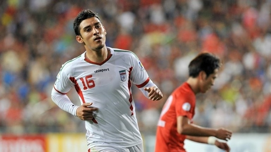 Iran's forward Reza Ghoochannejhad (left) celebrates after scoring against South Korea during their World Cup qualifier match against South Korea in Ulsan, southeast of Seoul on June 18, 2013.. Asian giants Iran, South Korea and Australia reached the 2014 World Cup but Uzbekistan narrowly failed to book their place on a dramatic night of action.