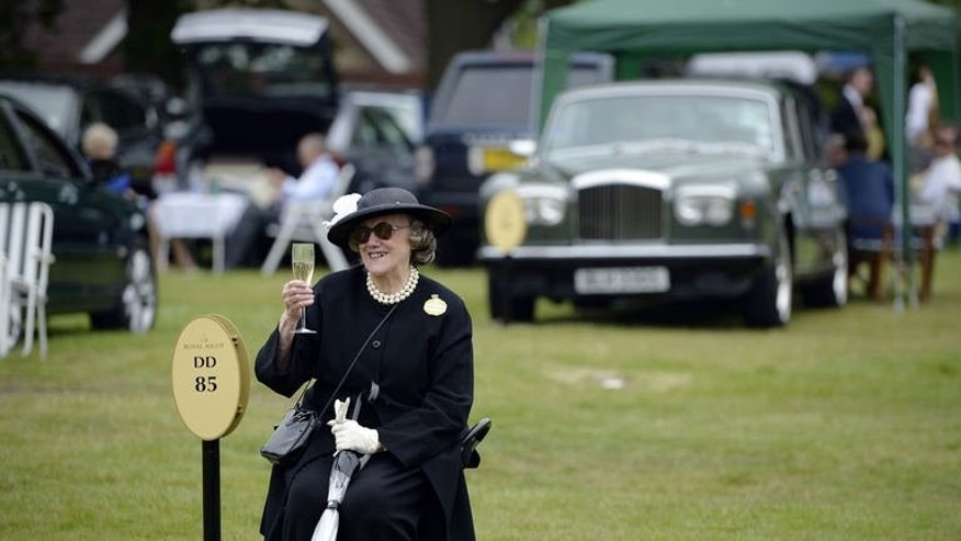 A racegoer raises a glass of champagne while she waits for friends during the first day of Royal Ascot, in Berkshire, west of London, on June 18, 2013. Ireland dominated the opening day of the Royal Ascot meeting on Tuesday carrying all before them in the first four races including the feature race the St James's Palace Stakes.