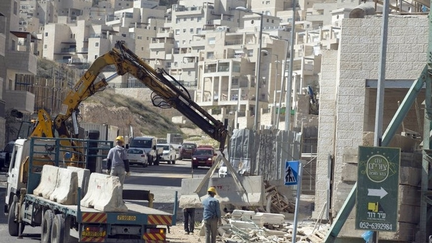 Labourers work at a housing construction site in the Israeli settlement of Har Homa in east Jerusalem on February 27, 2013. Israeli Housing Minister Uri Ariel implied that a silent freeze on new housing projects in east Jerusalem and the West Bank has been in place since the beginning of 2013.