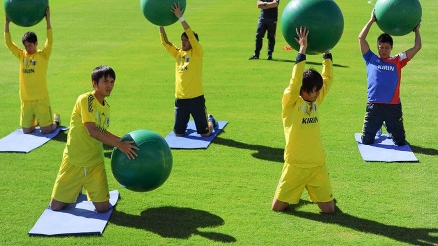Japan's Ryoichi Maeda (2nd L) and Yasuhito Endo (2nd R) stretch during a training session at Walmir Campelo Bezerra stadium in Gama, surburban Brasilia, on June 16, 2013. The task facing both, Asian champions Japan and three-time world champions Italy is clear cut in Recife at the Confederations Cup, on Wednesday.