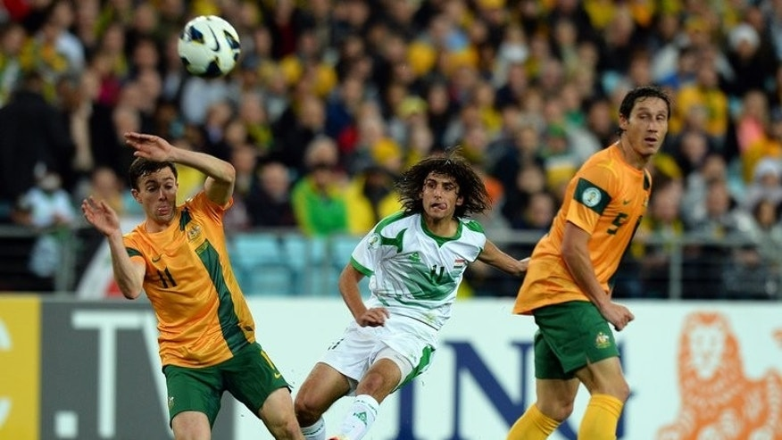 Iraq's Human Tareq Faraji (centre) clears the ball between Australia's Tommy Oar (left) and Rhys Williams during their World Cup qualifier in Sydney on June 18, 2013. Australia secured their place at the 2014 World Cup finals in Brazil with a late strike from Josh Kennedy firing them to a tense 1-0 win over an under-strength Iraq at Stadium Australia.