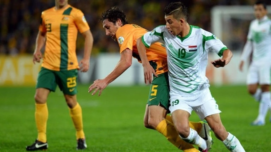 Australia's Rhys Williams (centre) vies for the ball with Iraq's Dhurgham Ismael Dawoodi during their World Cup qualifier in Sydney on June 18, 2013. Australia beat Iraq 1-0 to become only the second country to reach next year's World Cup in Brazil through qualifying.