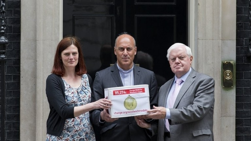 "The Rector of Woolwich Reverend Jesse van der Falk (centre) poses for photographers with his wife Louise (left) and councillor John Fahy (right), outside 10 Downing Street as they present a petition calling for the George Medal to be awarded to three women dubbed the ""Angels of Woolwich"", in London on June 18, 2013."