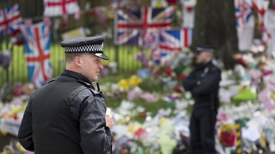 "Police officers stand beside floral tributes at the scene of the murder of British soldier Lee Rigby outside Woolwich Barracks, southeast London on June 1, 2013. Campaigners presented a petition to Downing Street on Tuesday calling for three women who known as the ""Angels of Woolwich"", who intervened after the murder of soldier Lee Rigby, to receive medals for bravery."