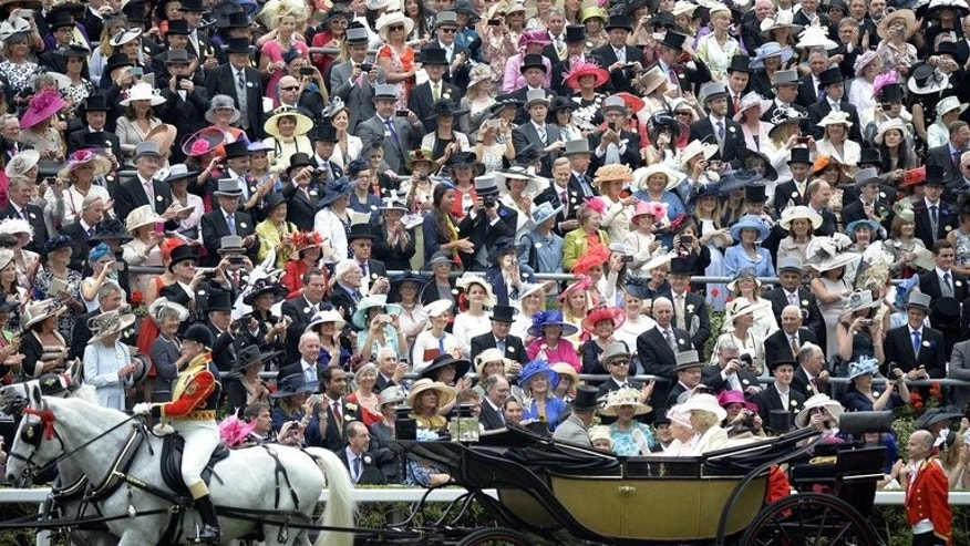Racegoers crowd around the parade ring as Britain's Queen Elizabeth II, Camilla, Duchess of Cornwall and Prince Charles arrive in a carriage during the first day of Royal Ascot, in Berkshire, west of London, on June 18, 2013. Queen Elizabeth II led tributes to Henry Cecil, the legendary trainer who died last week, before the start of racing at Royal Ascot on Tuesday.