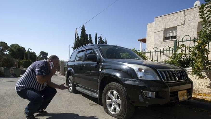 "An Arab Israeli man speaks on his mobile phone as he looks at the punctured tyres of his vehicle in the Arab Israeli town of Abu Ghosh, west of Jerusalem on June 18, 2013. Suspected Jewish extremists punctured the tyres of 28 cars in an Arab Israeli town and scrawled graffiti nearby in a likely ""price tag"" attack overnight."