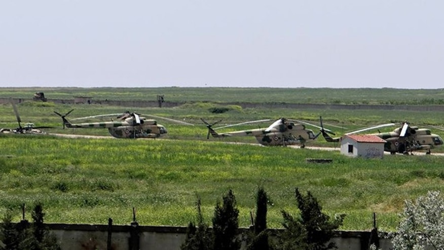 June 18, 2013: This citizen journalism image provided by Aleppo Media Center AMC which has been authenticated based on its contents and other AP reporting, shows Syrian military helicopters at Mannagh air base in Aleppo province, Syria. Syrian warplanes bombed rebel positions near a contested military air base in the north of Syria on Tuesday, activists said, while President Bashar Assad's forces nearby pressed ahead with an offensive against opposition fighters in the country's largest city Aleppo.