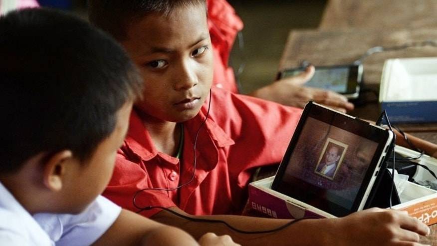 A student displays a picture of King Bhumibol Adulyadej on a tablet at the Ban San Kong school. In a rural classroom in the Thai highlands, hill tribe children energetically slide their fingertips over tablet computer screens practicing everything from English to mathematics and music.