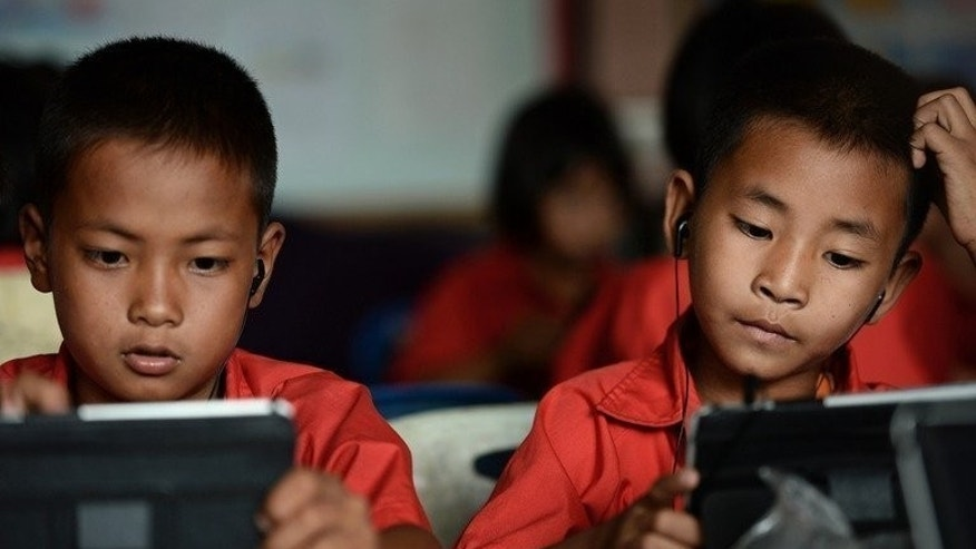 Students use tablets at Ban San Kong school in Mae Chan, in Thailand's northern Chiang Rai province. For opponents of the tablet plan, however, it is an expensive gimmick designed to boost the popularity of the ruling party among parents -- and the next generation of voters.