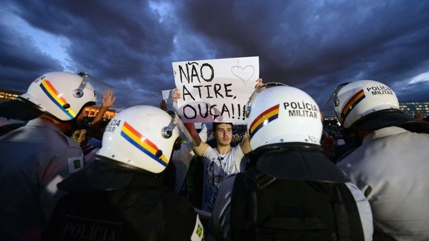 "A student holds a sign reading ""Don't shoot, listen!!!"" during a protest in the gardens of the National Congress, on June 17, 2013 in Brasilia. Brazil's president said Tuesday that the voices of hundreds of thousands of protestors across the country, angered by the cost of hosting sporting events such as the World Cup, must be heard."