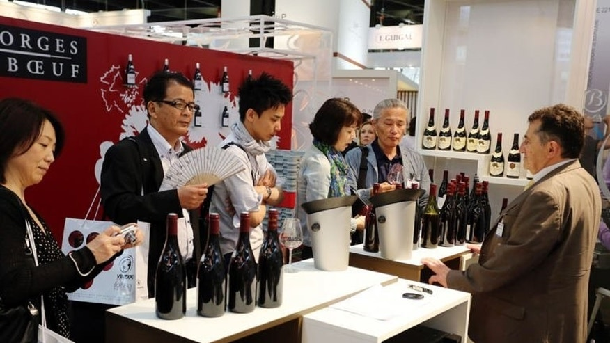 Asian buyers discuss with a French wine producer during the Vinexpo trade fair in Bordeaux, southwestern France, on June 17, 2013. Chinese wine importers have already started putting orders from France and other European countries on hold over fears of a hike in tariffs being triggered as part of a broader EU-China trade dispute, say leading figures in the sector.