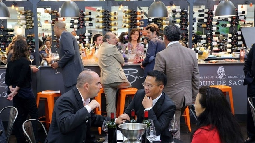 People taste wines during the Vinexpo trade fair in Bordeaux, southwestern France, on June 17, 2013.