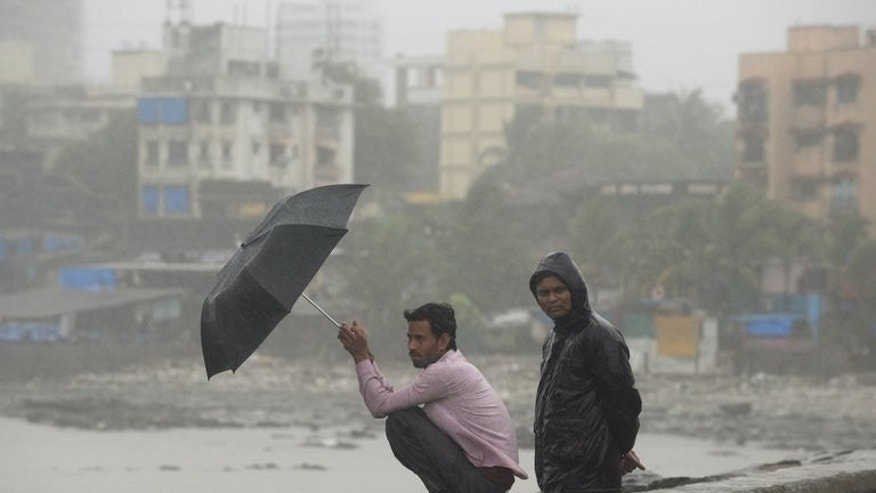 Local residents look out to the sea during heavy rain in Mumbai, on June 18, 2013. Military helicopters carried out emergency food drops on Wednesday for thousands of people stranded by flash flooding from early monsoon rains which have killed at least 120 in northern India.