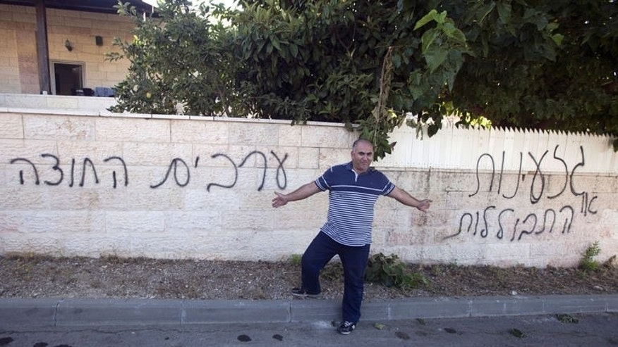 "An Arab Israeli man points to Hebrew graffiti that reads ""Arabs out"" (L) and ""assimliation"" (R), a negative reference to Jews and non-Jews mixing, on the wall of a house in the Arab Israeli town of Abu Ghosh on June 18, 2013. Suspected Jewish extremists slashed tyres and scrawled racist graffiti in the normally calm town on early Tuesday."