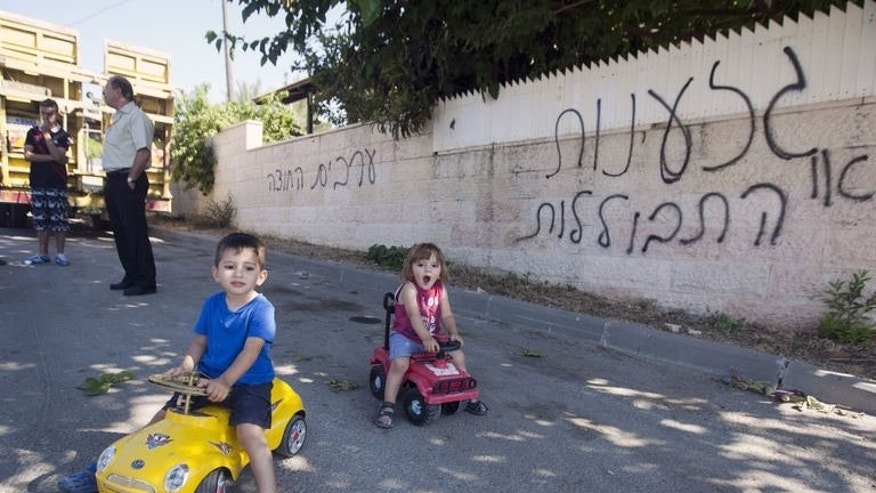 "Arab Israeli children ride their toy cars in front of graffiti that reads in Hebrew ""Arabs out"" (L) and ""assimliation"" (R), a negative reference to Jews and non-Jews mixing, in Abu Ghosh, on June 18, 2013."