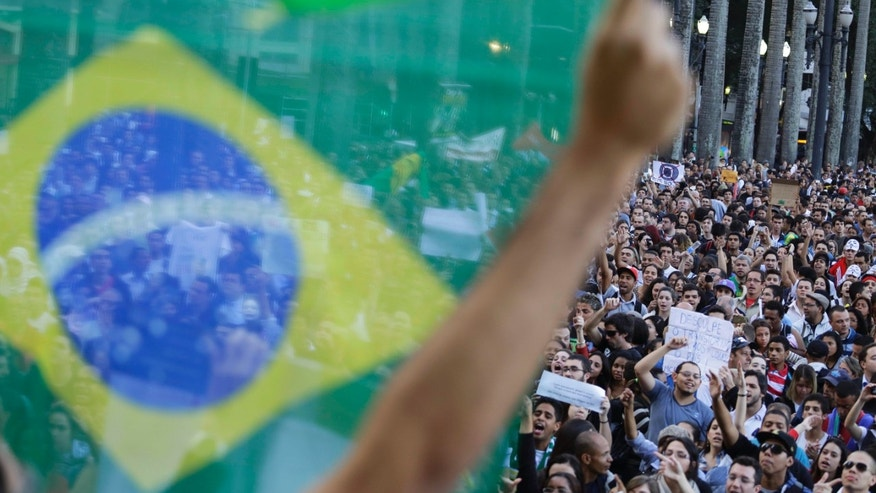 A demonstrator holds up a Brazilian flag in front of a group of protestors gathered in the main plaza of Sao Paulo, Brazil, Tuesday, June 18, 2013. Some of the biggest demonstrations since the end of Brazil's 1964-85 dictatorship have broke out across this continent-sized country, uniting multitudes frustrated by poor transportation, health services, education and security despite a heavy tax burden. (AP Photo/Nelson Antoine)