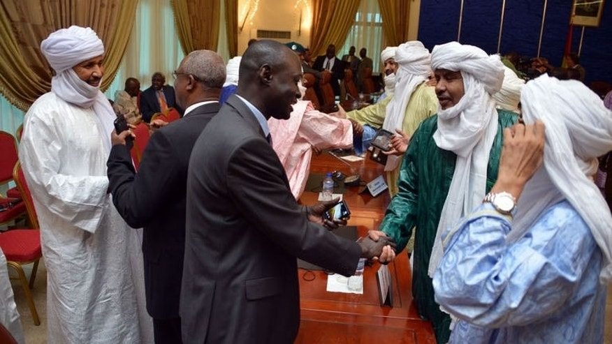 Members of the Malian and Tuareg delegations shake hands after signing an agreement at a meeting on the Malian crisis on June 18, 2013 in Ouagadougou. The clock is ticking for Mali as it scrambles to organise key elections in less than 40 days following a ceasefire deal between the government and separatist Tuareg rebels.