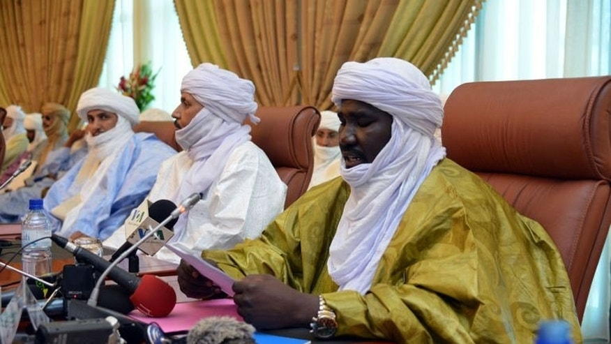 The vice president of MNLA Mahamadou Djeri Maiga (R) reads a document on June 18, 2013 during negotiations with the Malian government in Ouagadougou.