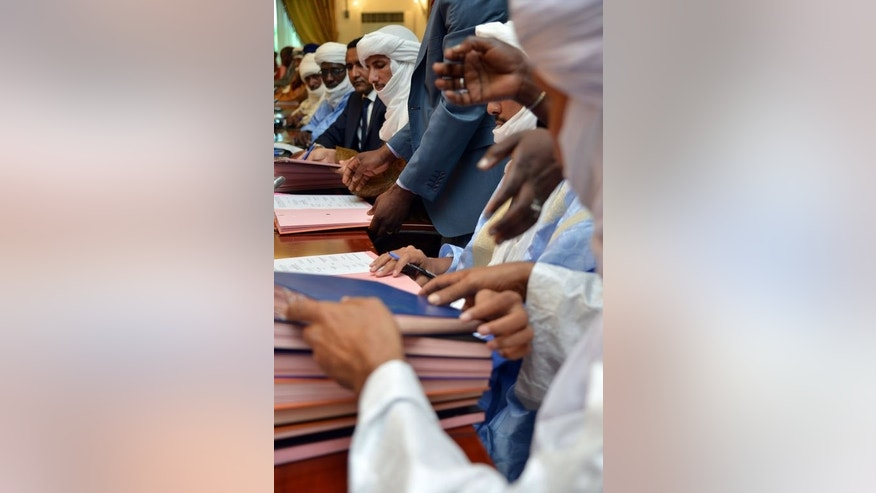 Alghabass Ag Intalla (C), leader of the Ansar Dine delegation, signs an agreement at a meeting on the Malian crisis on June 18, 2013 in Ouagadougou.