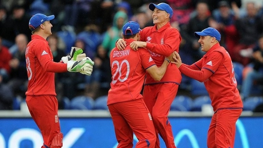 England's Joe Root (2nd R) celebrates during the Champions Trophy match against New Zealand on June 16, 2013. England were lucky the weather favoured them on Sunday as the hosts squeezed out a 10-run win over New Zealand in a game reduced to 24-overs-a-side due to rain.