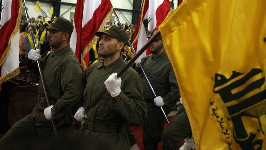 "Hezbollah fighters march with a yellow Hezbollah flag and Lebanese national flags in Beirut in 2008. ""Hezbollah fighters, who have a strong presence at Sayyida Zeinab (in southeastern Damascus), are trying to seize control of villages near Zayabiyeh and Babila,"" says the Syrian Observatory for Human Rights."