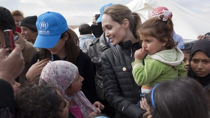 "Angelina Jolie (centre) meets refugees at the Zaatari refugee camp in Jordan near the Syria border last December. Jolie has urged the international community to boost aid to Syrian refugees hit by what she called ""the worst humanitarian crisis of the 21st century,"" a UNHCR statement said Wednesday."