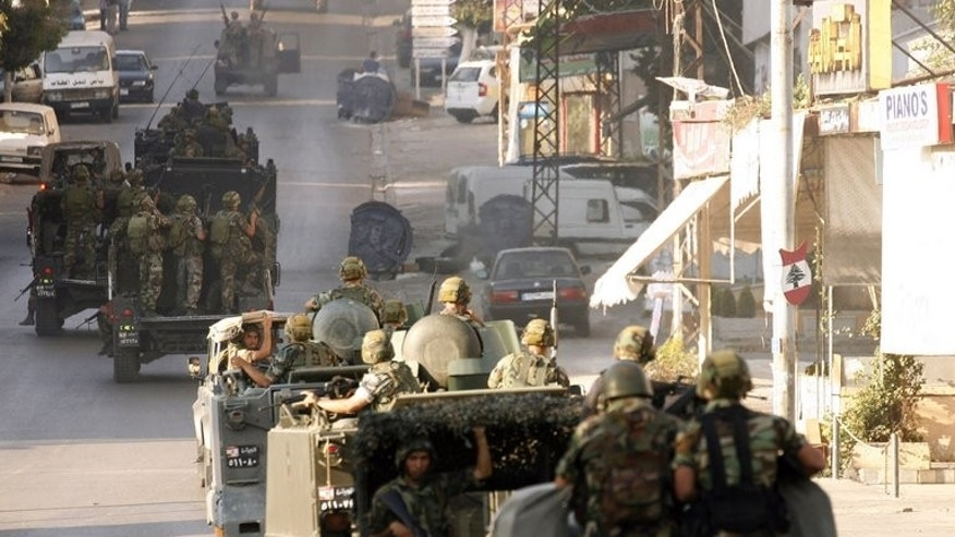 "The Lebanese army deploys in the southern town of Sidon's eastern suburb of Abra, on June 18, 2013 after a shooting by gunmen loyal to the controversial Sunni Salafist Sheikh Ahmed al-Assir. The sheikh threatened on Wednesday to find a ""military"" solution to alleged Hezbollah safehouses in the southern Lebanese town,."