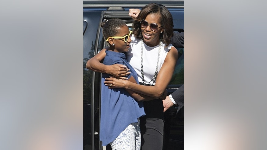 US first lady Michelle Obama hugs her daughter Sasha as they arrive to visit the Holocaust Memorial to the Murdered Jews of Europe in Berlin on June 19, 2013. As President Barack Obama attended to matters of state during a 24-hour visit to the German capital, his family had a rather sombre sightseeing schedule.