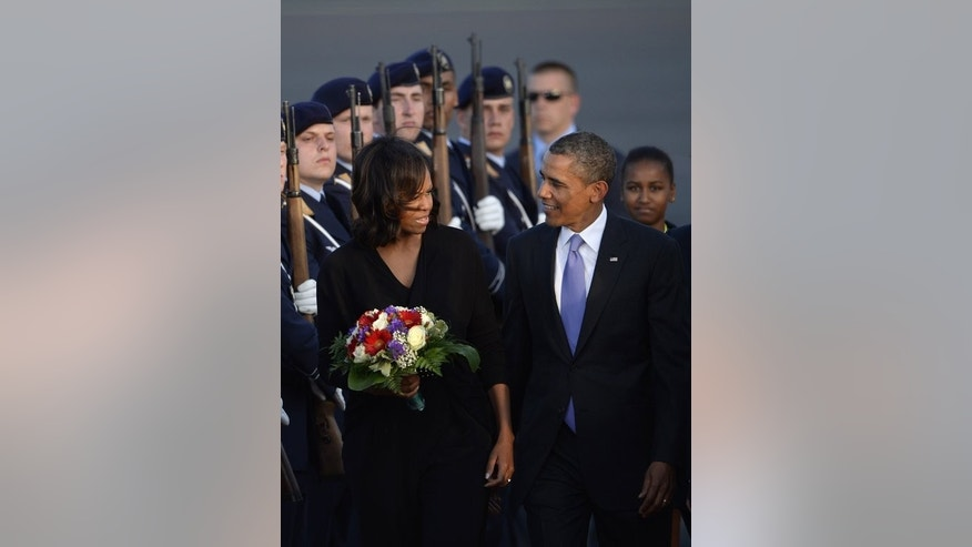 US President Barack Obama and US first lady Michelle Obama review the guard of honour upon arrival at Berlin Tegel airport on June 18, 2013. US First Lady Michelle Obama and her two daughters, Malia and Sasha, on Wednesday visited Berlin's Holocaust Memorial as part