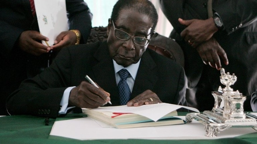 Zimbabwe President Robert Mugabe signs into law the Zimbabwe draft constitution in Harare, on May 22 2013. Mugabe has filed an urgent application with the country's top court to push back crucial elections by two weeks, his justice minister says.